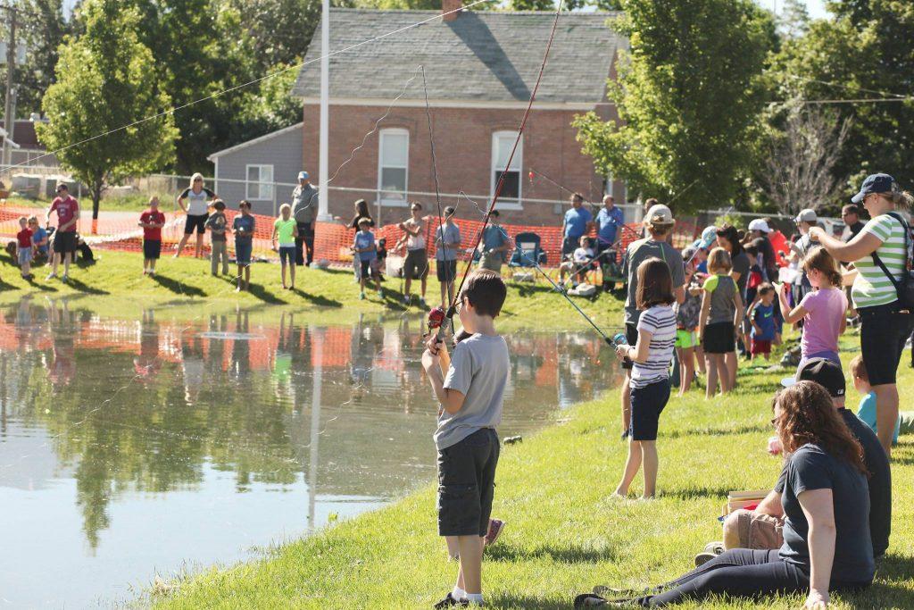 kids standing around at a lake fishing